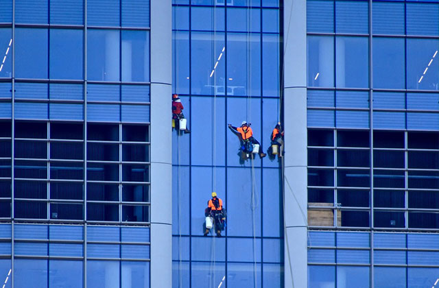 Window cleaners scale a skyscraper cleaning windows