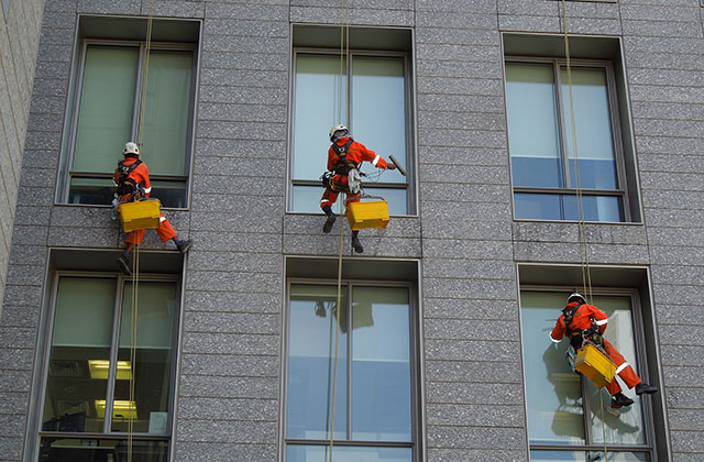 Window cleaners scale an apartment cleaning windows